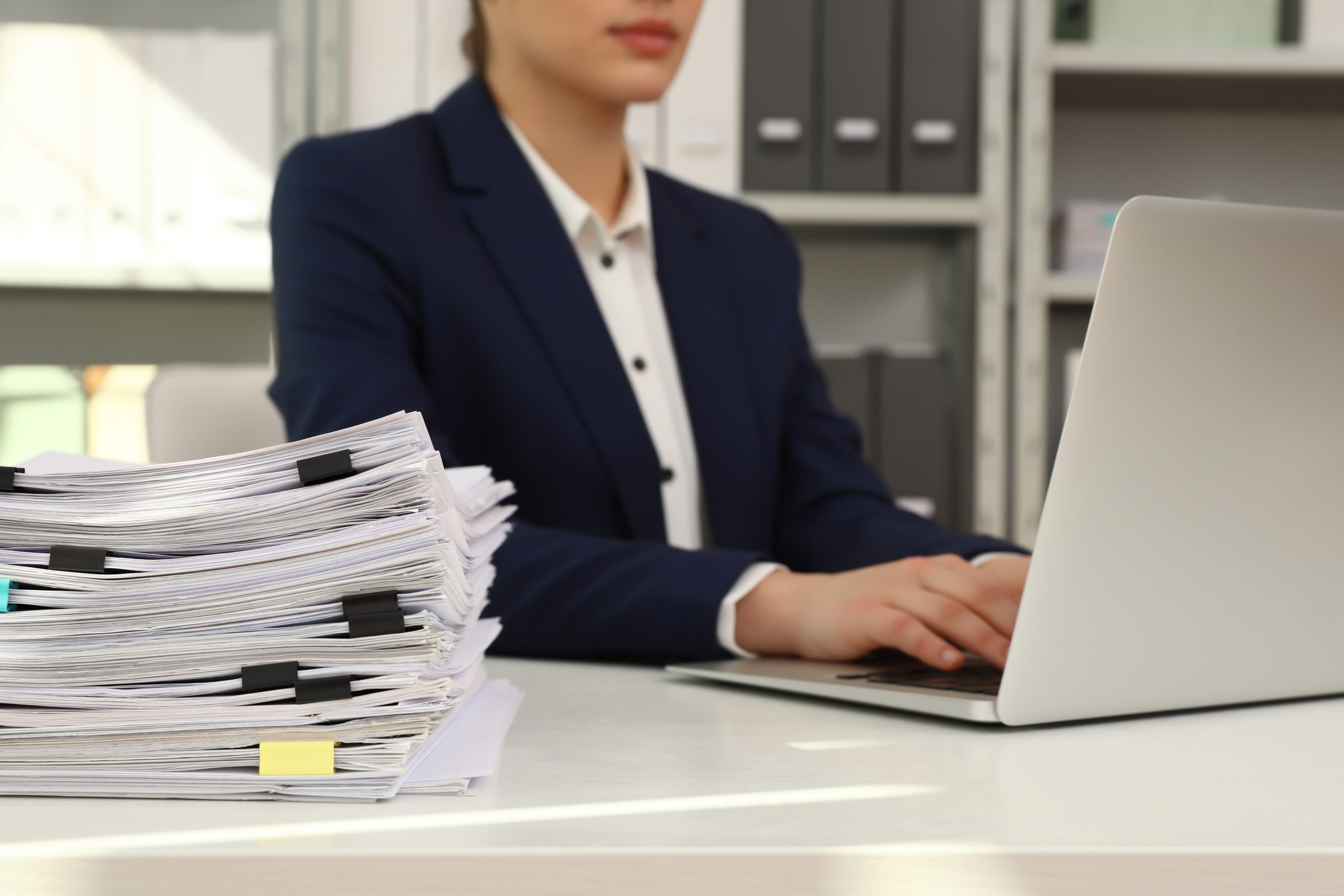 Female worker working with laptop near stack of documents in office, closeup